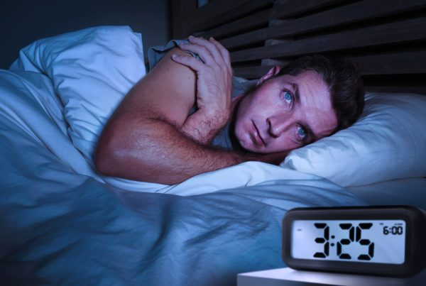 Man awake in bed from side effects of Jet lag, DiaResQ